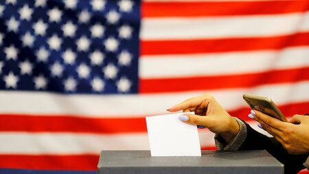 woman putting a ballot in a ballot box on election day. Close up of hand with white votes paper on usa flag background Stockfoto