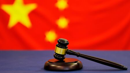 Judges gavel. Symbol for jurisdiction. Law concept a wooden judges gavel on table in a courtroom or law enforcement office on blue background. China flag background Stock fotó