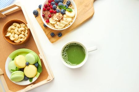 matcha green tea, breakfast top view white background. oatmeal with berries, toasts on a wooden tray, nuts, coffee. Stock fotó
