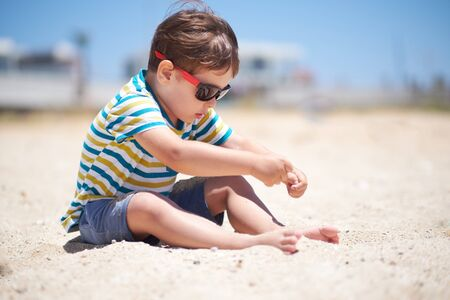 holiday, little boy three years old fun digging in the sand at the beach. Stock fotó