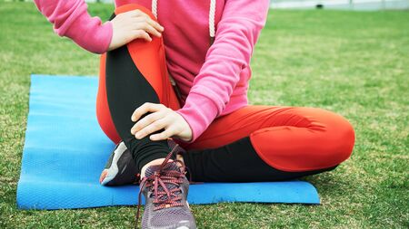 Female athlete suffering form running knee or kneecap injury during outdoor workout on dirt road