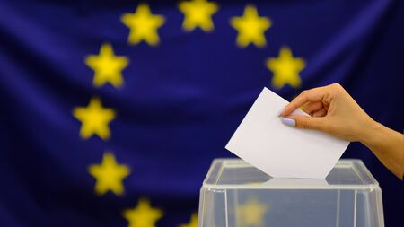 Hand holding ballot paper for election vote concept. elections, The hand of woman putting her vote in the ballot box. on european union flag background