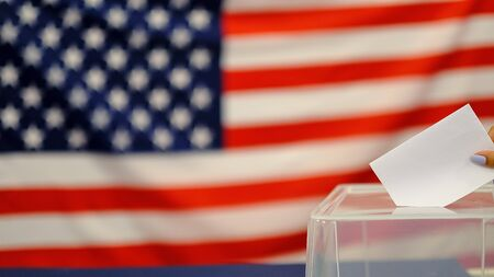 woman putting a ballot in a ballot box on election day. Close up of hand with white votes paper on usa flag background Banque d'images
