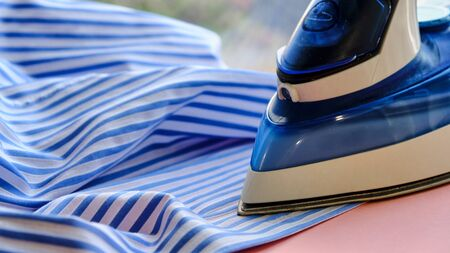 Electric iron and shirt on ironing board in room on a pink background. iron blue striped shirt.