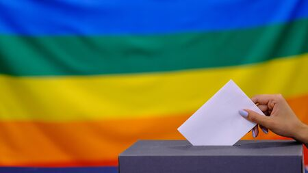 Hand holding ballot paper for election vote concept. elections, The hand of woman putting her vote in the ballot box. Rainbow flag on background