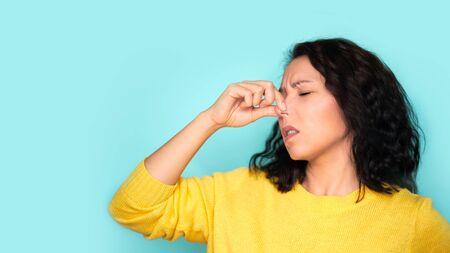 femme sentant quelque chose de puant et dégoûtant, odeur intolérable, retenant son souffle avec les doigts sur le nez. Mauvaises odeurs