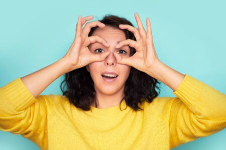 funny young woman holding fingers near eyes on a blue background Foto de archivo
