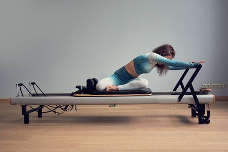 entrenamiento de leotardo entrenamiento de pilates. ejercicios atléticos reformer pilates. equipo de maquina de pilates. Joven mujer asiática pilates estiramiento deporte en reformador cama instructor niña en un estudio.