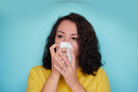 Burnette woman blowing nose into tissue. Flu cold or allergy symptom. Sick woman girl sneezing in tissue on blue. Health care. Stock Photo