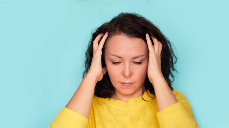 Young Asian girl scratches her hair on a blue background. headache