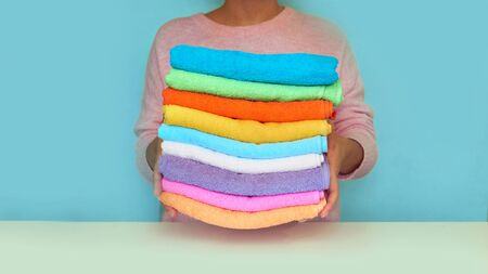 Close-up of hands putting stack of fresh bath towels. multi-colored rolls of towels in a wicker basket on a blue background