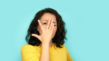 cheerful female covering her face using hands on a blue background 版權商用圖片
