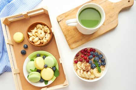 matcha green tea, breakfast top view white background. oatmeal with berries, toasts on a wooden tray, nuts, coffee