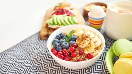 breakfast top view isolate white background. oatmeal with berries, toasts on a wooden tray, nuts, coffee