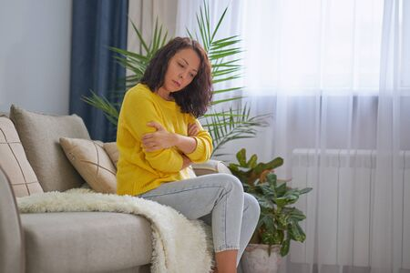 Woman Suffering From Depression Sitting On Bed In Pajamas 版權商用圖片