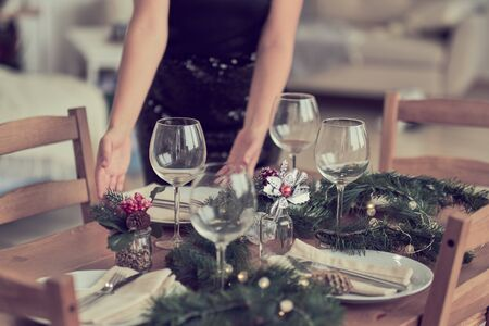 woman is waiting for guests and sets the table. festive laying table, preparation for christmas dinner.
