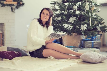 Woman reading book in front of Christmas tree