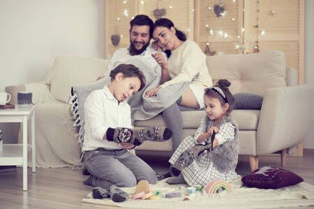 little boy girl having fun, friendship between siblings, family leisure time in living room. Children sister and brother playing drawing together on floor while young parents relaxing at home on sofa