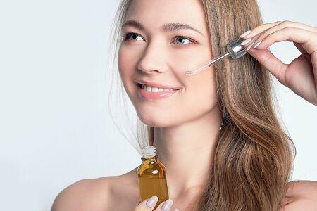 beautiful model applying a skin serum treatment on white. Spa, skincare and wellness. Close up, copyspace