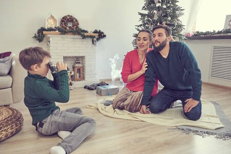 son takes pictures of dad and mom. couple posing under christmas tree for photographer s son