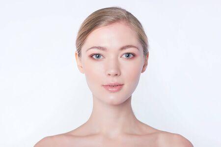 Retrato de primer plano de una chica hermosa, fresca, sana y sensual sobre fondo azul.