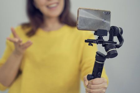 attractive asian woman blogger or vlogger looking at camera and talking on video shooting with technology. Social media influencer people Stok Fotoğraf