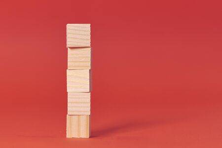 brown wood bricks tower. construction from wooden cubes. on red background Banco de Imagens