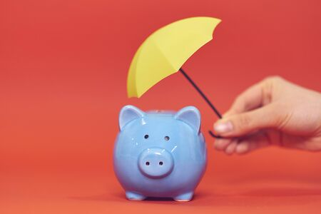 Piggy bank with a yellow umbrella on a red background. savings accumulation