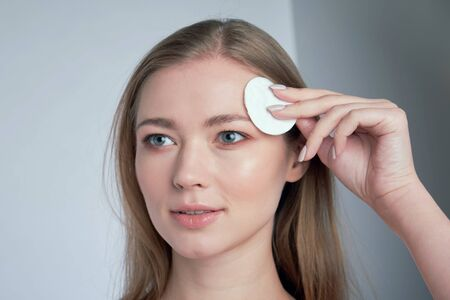 Healthy fresh girl removing makeup from her face with cotton pad. woman with a sponge wihte background cotton pad problem skin