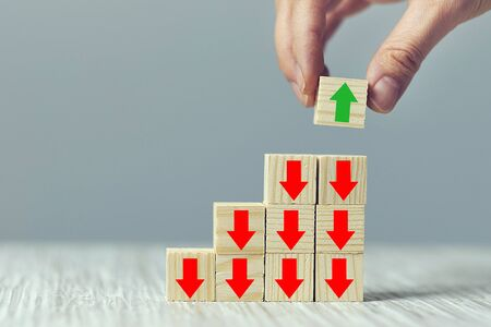 Hand arranging wood block stacking as step stair on wooden table. alternative thinking, change of direction. all arrows down one up. Stock Photo