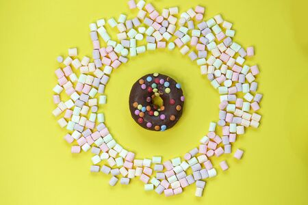 donut in a round marshmallow frame on a yellow background. top view photo Фото со стока - 140960666