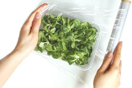 Woman using food film for food storage on a white table. Roll of transparent polyethylene food film for packing products.
