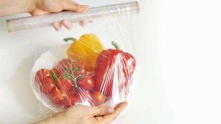 Woman using food film for food storage on a white table. Roll of transparent polyethylene food film.
