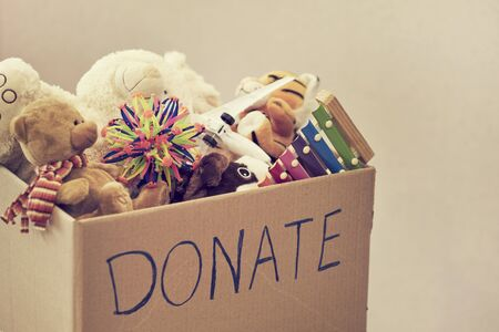 Donation box with children toys. woman collects toys for charity. Stockfoto