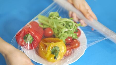 Woman using food film for food storage on a white table. Roll of transparent polyethylene food film. Standard-Bild