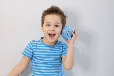 little asian boy holds a piggy bank in his hands. money saving concept