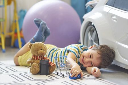little boy plays alone in a children's room and uses a smart house card to listen to fairy tales Archivio Fotografico