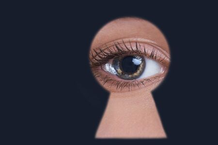 woman peeping through keyhole, concept of gossip, espionage. Close-up Photo Of Persons Seen Through Keyhole
