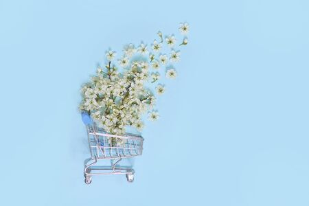 flowers fly out of the shopping cart on a blue background. spring shopping concept. seasonal sale.