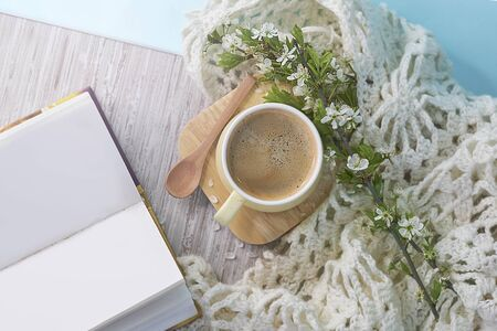 Cozy home still life: cup of hot coffee, spring flowers and opened book with warm plaid. Springtime concept, free copy space. close up top view