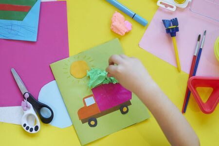 School supplies, stationery on yellow background - space for caption. Child ready to draw with pencils and make application of colored paper.