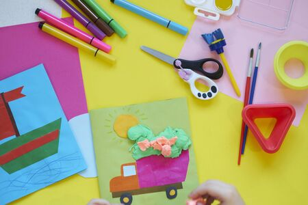 School supplies, stationery on yellow background - space for caption. Child ready to draw with pencils and make application of colored paper. Top view. Archivio Fotografico