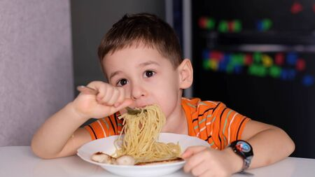 funny Little boy eat pasta in the kitchen table.