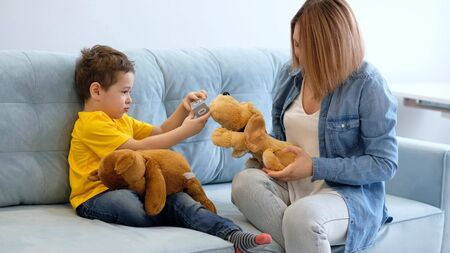View of mother having fun with baby. mother and son playing with toy on sofa. have fun together. mom is trying to make contact with her hyperactive son