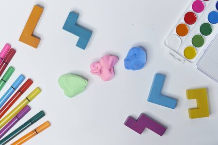 felt-tip pens, cubes, paints and plasticine on a white background. children's desktop. School, education and learning concept. creativity for kids. Top view colorful background.