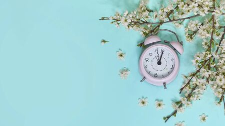 Pink alarm clock and delicate little white flowers on blue background. Top view. Time for love and greetings. Spring Time Change, Spring flowers and Alarm Clock