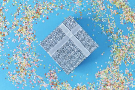gift box with blue ribbon, confetti and balls