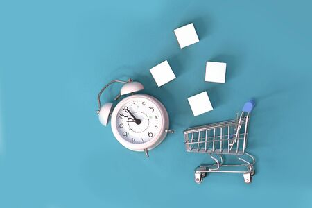 Fast delivery, time value of money concept : clock - silver shopping cart or a supermarket shopping basket on blue background Фото со стока
