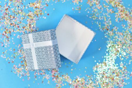 Open empty gift box with blue ribbon, confetti and balls