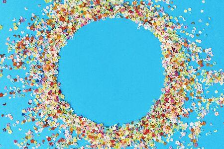 Round frame made of colored confetti. blue background. Festive confetti.